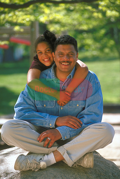 portrait of smiling girl embracing father at park