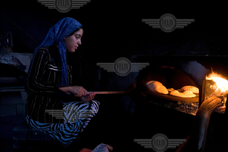 A young woman from the Abu Quaider family, cooks bread in her home in the unrecognised Bedouin village of Al Zarnock in the Negev desert. Around 75,000 Bedouin people who live in this region are in unrecognised villages. The villages are not acknowledged by the state of Israel, and lack basic infrastructure, nor do they appear on any offical maps of the country.