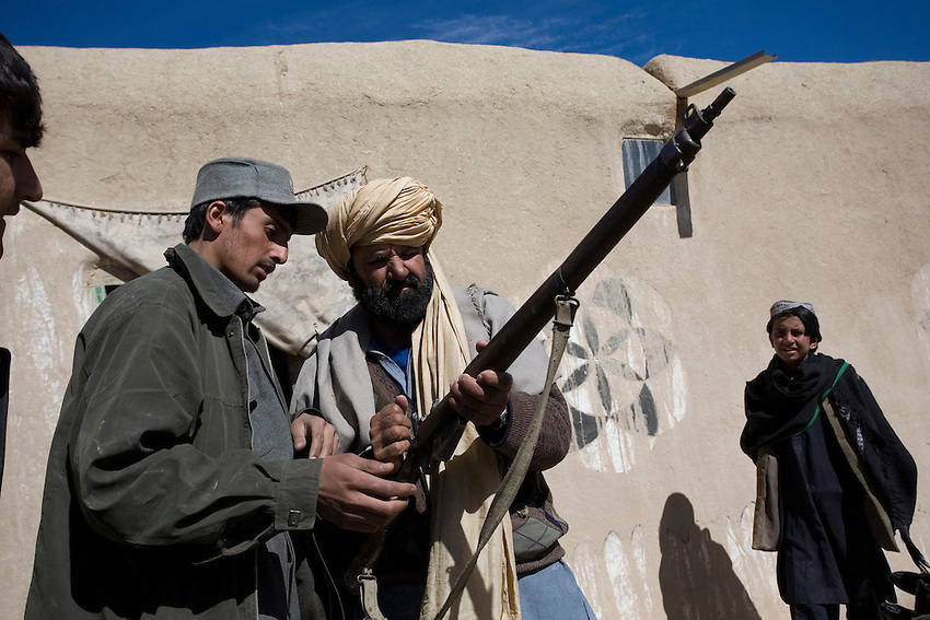 A member of the Afghan National Police inspects a villagers vintage rifle in Gabikhel, Paktika Province, Afghanistan, Sunday, Feb. 15, 2009. The weapon was not confiscated.
