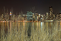 Midtown Manhattan Skyline at Night Viewed Thru Grass at the Edge of the East River Waterfront in Queens, New York City, New York State, USA   <br />