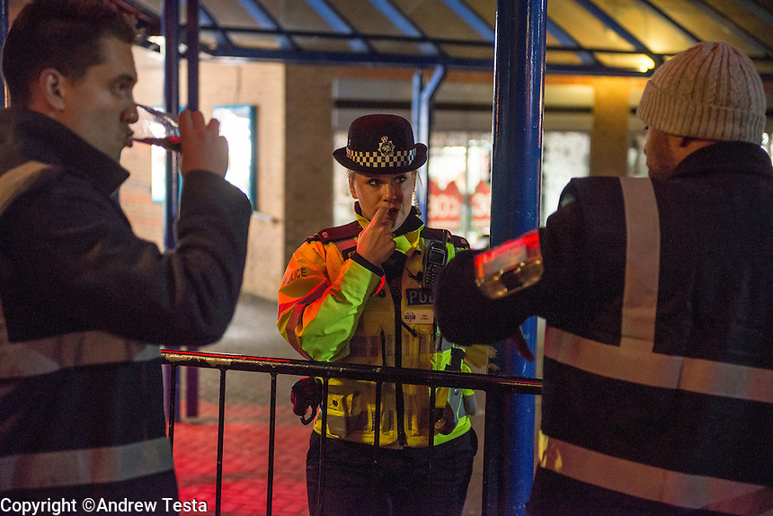 UK. Northampton. 7th December 2013<br /> Policewomen Amy Lovell talks to night club doormen outside a club in Northampton.<br /> &copy;Andrew Testa for the New York Times
