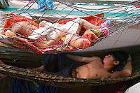 Phnom Penh, Cambodia. Central Market. Man and baby napping in a hammock.