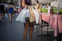A shopper with her collection of plastic bags at the Union Square Greenmarket in New York on Wednesday, August 21, 2013. Members of the NY City Council are proposing a bill that would require merchants to charge shoppers 10 cents for every bag used in order to encourage people to reuse or bring their own bags. (© Richard B. Levine)