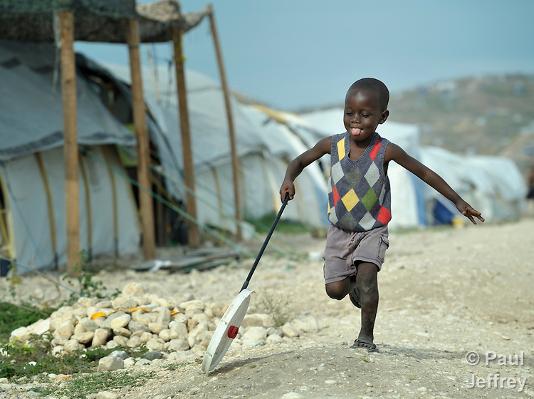 Aptul Regist, 4, pushes a homemade toy through a portion of the Corail resettlement camp north of Port-au-Prince, Haiti. Residents of the camp, survivors of the devastating January 2010 earthquake, were relocated to the remote location from overcrowded tent cities for the homeless in the nation's capital. Yet shortly after its establishment, thousands of homeless families from around the capital region moved to the area and began constructing their simple homes around the edges of the official camp, creating a complex set of questions for camp managers. The United Methodist Committee on Relief, a member of the ACT Alliance, has built schools in the camp and is providing school furniture, teacher training, and educational materials for students.