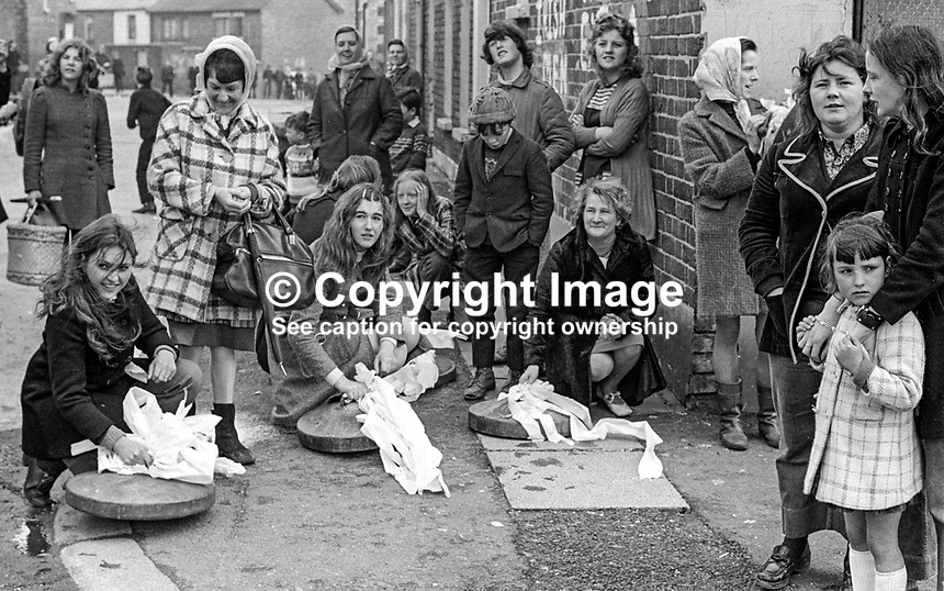 Friends and neighbours waiting with bin lids at the ready await Republican internee Sean McClenaghan, 19 years, and his bride, Sadie McCauley, 17 years, after their wedding at Holy Cross Chapel, Ardoyne, Belfast, N Ireland, on 8th April 1972. Rattling bin lids to warn of a police or military presence became a tradition in republican areas of Belfast. Mr McClenaghan was given 24 hours parole for his wedding and honeymoon! 197204080177b..Copyright Image from Victor Patterson, 54 Dorchester Park, Belfast, United Kingdom, UK...For my Terms and Conditions of Use go to http://www.victorpatterson.com/Victor_Patterson/Terms_%26_Conditions.html