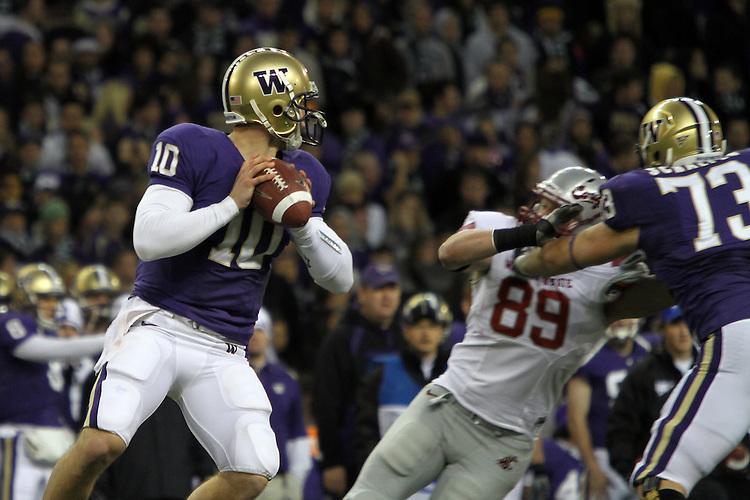 Jake Locker (#10), University of Washington quarterback, tries to stay in the pocket while looking for an open receiver during the Huskies Pac-10 conference football game against arch-rival Washington State at Husky Stadium in Seattle, Washington, on November 28, 2009.  Washington shut out the Cougars in their annual Apple Cup battle, 30-0.