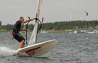 Surfen im Schladitzer See. Erst zum zweiten Mal in dieser Surfsaison erreichte der Wind im Tagesdurchschnitt 5 Beaufort, was einer Geschwindigkeit von 29 bis 38 km/h entspricht. Je mehr der Wind blaest, desto kleiner kann das Brett und das dazugehoerige Segel gewaehlt werden. Dann machen Tricks am meisten Spass.  im Bild: Dieser Surfer setzt zur Halse an, einer Wende bei der Surfer seine Geschwindkeit nutzt, um das Segel zu shiften. Im Hintergrund ist die Roba und der Schladitzer Strand zu sehen.  Foto: Alexander Bley.