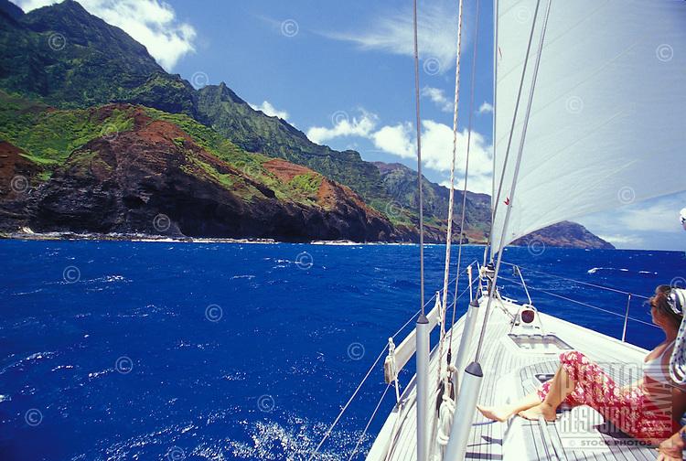 Woman looking at seacliffs of Kauai's Na Pali Coast from deck of sailing yacht