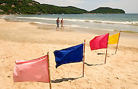 A couple strolls along Playa la Ropa beach past colorful flags that mark the take-off areas for parasailing. Playa la Ropa Beach, located on Zihuatanejo Bay, is one of the most popular beaches in Zihuatanejo/Ixtapa.  (taken August 2007). Photo by Patrick Schneider Photo.com