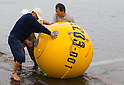 (File Photo) Hiratsuka, Japan - In the file photo released on November 25, 2011 shows Cosmo Power Co., Ltd. employees doing a live demonstration of Noah's Ark at a port in Hiratsuka, Kanagawa Prefecture, October 20, 2011. Shoji came up with the idea to make Noah's Ark after watching the torrential rain that hit Kyushu approximately 4 years ago. His primary vision for the company is to make products that can save as many people in the future from large natural disasters. The construction process to fully complete a single capsule takes one day but the company aims to make 20 per day. There are currently two models of the safety capsules that can fit up to 4 people (1,200mm) (priced at 315,000 Japanese Yen) and 6 people (1,500mm) (priced at 471,450 Japanese Yen). There has been a demand of buyers for Noah's Ark from countries such as the United States, Brazil, China, Thailand, Bangladesh and New Zealand, however, the company is not ready to sell overseas at present. Shoji mentioned that he plans to make a more advanced model of Noah's Ark in the near future. (Photo by: Christopher Jue/AFLO)