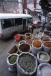 A streetside market with bags of seeds, spices, and dried food products in the city of Fengjie China
