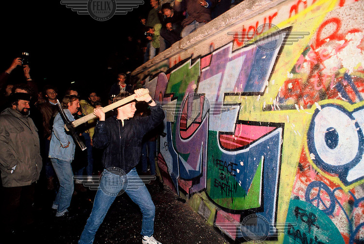 A man attacks the Berlin Wall with a pickaxe on the night of November 9th, 1989 as news spread rapidly that the East German Government would now start granting exit visas to anyone who wanted to go to the West. The announcement was misinterpreted as meaning the border was now open and East German border guards were unable to stop the rush of people to the Wall. Within hours people were smashing sections of the Wall with their own hand tools and these first cracks led to the complete opening of the border within days.