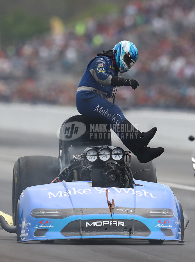 Mar 16, 2019; Gainesville, FL, USA; NHRA funny car driver Tommy Johnson Jr climbs from his car after exploding the body off his car during qualifying for the Gatornationals at Gainesville Raceway. Mandatory Credit: Mark J. Rebilas-USA TODAY Sports