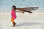 Five-year old Vera Vernanda plays on the beach at Lhok Me, in Indonesia's Aceh province. The girl's mother sells coconuts and soft drinks to tourists on the beach. The family was left homeless by the 2004 tsunami, but YEU, a member of the ACT Alliance, worked with the village to build new houses in a safer area, as well as help revitalize their income generating activities, including Vera's mother's small business. The tsunami killed 221,000 people in Aceh province and left more than 500,000 displaced.<br /> <br /> Parental consent obtained.