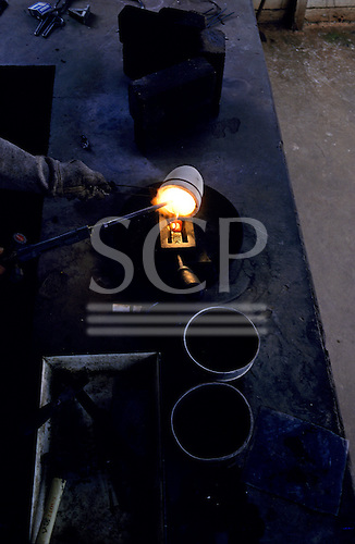 Para State, Brazil. Serra Pelada illegal goldmine (garimpo); smelting gold in a crucible with a gas blowtorch.