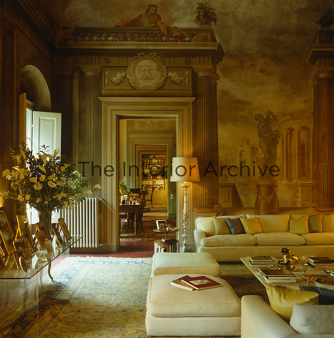 View of the enfilade of rooms leading from the drawing room of a Sicilian palazzo with classical mural