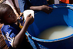 A young boy dips his cup into a plastic barrel of water before drinking during a celebration of the parish priest's 25th year being ordained in Lukeleli, Tanzania on November 16, 2008. The town had initially dug their wells too deep and due to a dry early rainy season they were not pumping correctly leaving most of the town to drink water that had come from much more shallow sources. This water has a much higher chance of being infected with animal runoff and other sources of negelected tropical diseases.