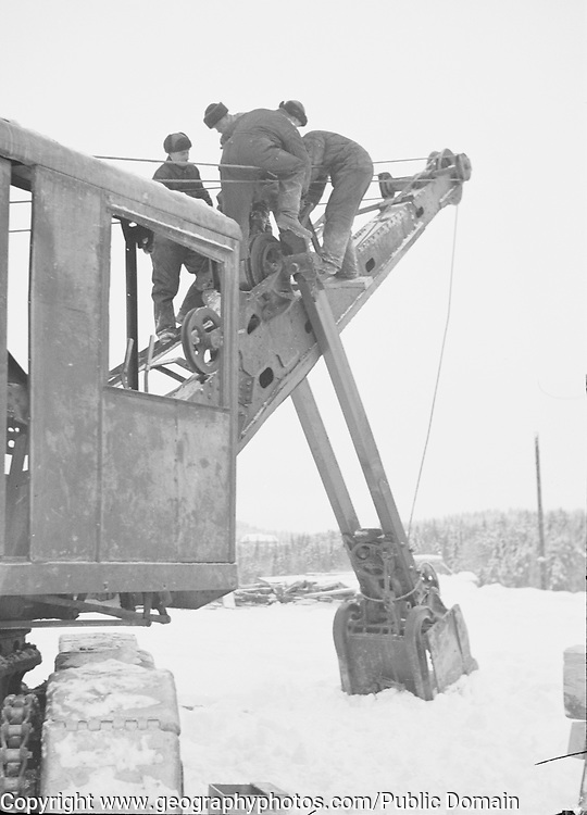 Four male workers operating machine excavator bucket in snow, Finland 1920s-1940s