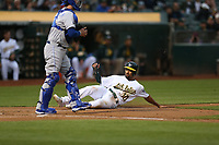 OAKLAND, CA - AUGUST 14:  Marcus Semien #10 of the Oakland Athletics slides home safely against the Kansas City Royals during the game at the Oakland Coliseum on Monday, August 14, 2017 in Oakland, California. (Photo by Brad Mangin)