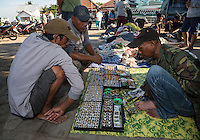 Jimbaran, Bali, Indonesia.  Potential Customers Examine Vendor's Selection of Rings and Necklaces.