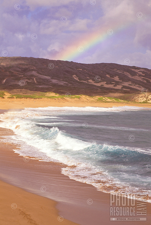 Unique Moomomi Dunes on Molokai's northwest shore is a treasure trove for endangered plant and animal species. Waves pound the shoreline of a pristine beach as a beautiful rainbow shimmers in the distance.