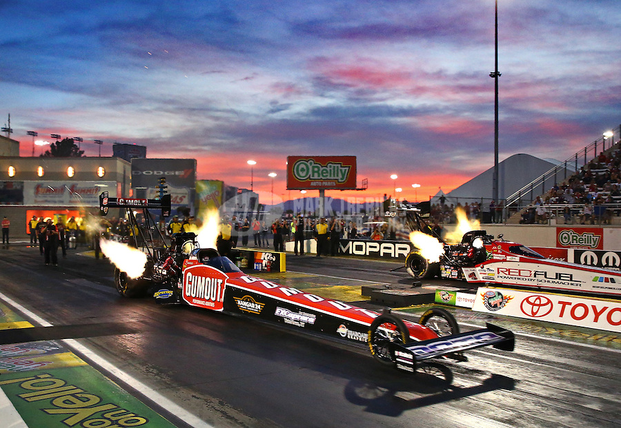 Oct 31, 2014; Las Vegas, NV, USA; NHRA top fuel driver Leah Pritchett (near) races alongside Spencer Massey during qualifying for the Toyota Nationals at The Strip at Las Vegas Motor Speedway. Mandatory Credit: Mark J. Rebilas-USA TODAY Sports
