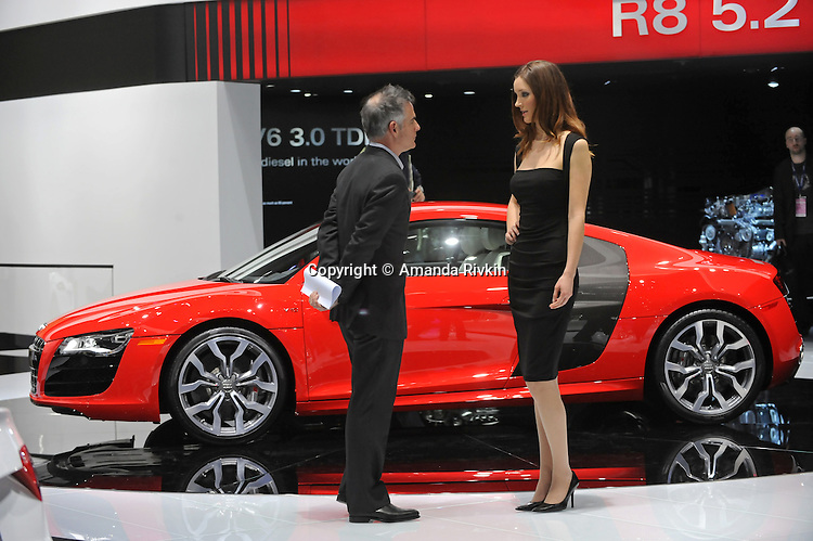 A man talks to a model beside the Audi R8 V10 in the Audi showroom at the Detroit Auto Show in Detroit, Michigan on January 12, 2009.