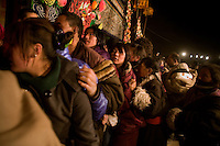 Monks control crowds of pilgrims during a prayer ceremony at night outside the Labrang Monastery during the Monlam Festival in Xiahe, Gansu, China.