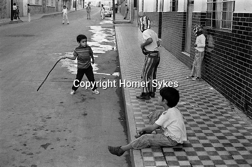 Mazatlan Mexico. Children playing a violet game in the street, boys wearing typical Mexican wrestling masks.No doubt influenced by watching to much TV.  1973.