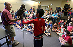 Gabe Kerschner, with Wild Things, helps Juan Brena, 12, hold Archimedes, a great horned owl, during a presentation at the Carson City Library, in Carson City, Nev., on Wednesday, July 30, 2014.<br /> Photo by Cathleen Allison