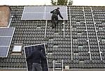 Foto: VidiPhoto<br /> <br /> VALBURG &ndash; Medewerkers van Mijn Energie Management uit Kesteren monteren zaterdag 33 hoogwaardige zonnepanelen op het dak van een vrijstaande woning in Valburg (gemeente Overbetuwe). Het aantal van 33 panelen is erg hoog voor een particuliere woning. De eigenaar wil niet alleen electriciteit aan het net leveren, maar op termijn de energie ook zelf opslaan, zodat hij onafhankelijk is van energieleveranciers en de overheid. Die laatste heeft namelijk een forse stijging van de energiebelasting aangekondigd. Mede om die reden zijn zonnepanelen op dit moment nauwelijks aan te slepen, aldus de installateur uit Kesteren die het werk nauwelijks aan kan. De enorme run op panelen heeft ook te maken met het verdwijnen van gas op termijn. In de gemeente Overbetuwe worden vanaf volgend jaar geen nieuwbouwwoningen meer aangesloten op gas. Bovendien houden particulieren zich via eigen co&ouml;peraties steeds vaker bezig met de opwekking en handel in duurzame stroom nu spaargeld niets meer oplevert. Dit jaar steeg het aantal energieco&ouml;peraties in Nederland met zestig tot 392, meldt kennisplatform HIER Opgewekt. Ook het aantal collectieve zon- en windprojecten neemt een vlucht. Circa 60 procent van de co&ouml;peraties verkoopt groene energie. Tot nu toe werden dit jaar 274 eigen windturbines of zonnedaken en -weides gerealiseerd. Deze projecten leveren genoeg stroom op voor 85.000 huishoudens. De verwachting is, dat het aantal zonprojecten in 2018/19 verdubbelt.