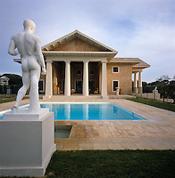 A classical statue stands sentinel over the swimming pool with the neo-Palladian villa designed by David Hicks beyond