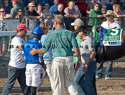 After It's Tricky dumped Eddie Castro, track officials and workers for trainer Kiaran McLaughlin make sure Castro's OK.