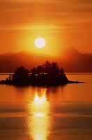 Alaskan landscape of sunset over a small island; the sun reflected on the water surface. Inside Passage, Alaska.
