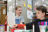NWA Democrat-Gazette/CHARLIE KAIJO Lliam Blue, 9, of Rogers (left) shows a collage he made to brother, Jameson Blue, 10, (right) during a collage making art session, Monday, September 9, 2019 at the Rogers Public Library in Rogers.<br /> <br /> The program is geared towards kids ages 5-12 inspired by the work of illustrator Eric Carle. Kids use a variety of materials like paint, scissors, glue, pom-poms, gems, marbles, geometric shapes, magazine cut-outs, markers and puzzle pieces to illustrate a weekly theme.