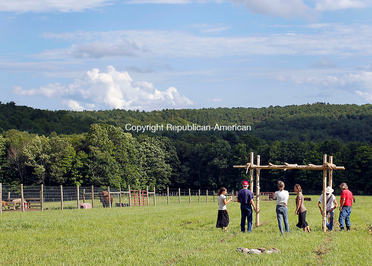 Goshen, CT-27 July 2012-072712CM02-  Men and women from various Native American Nations construct an arbor at Mohawk Bison Farm, owned by Peter Fay, Friday afternoon in Goshen.  The arbor  will be used to provide shade for Lakota elders, during a naming ceremony for a white bison calf that was born a little over a month ago.  Hundreds of people, are expected to show up for the ceremony which is set to take place today (Saturday) at Fay's Farm.       Christopher Massa Republican-American