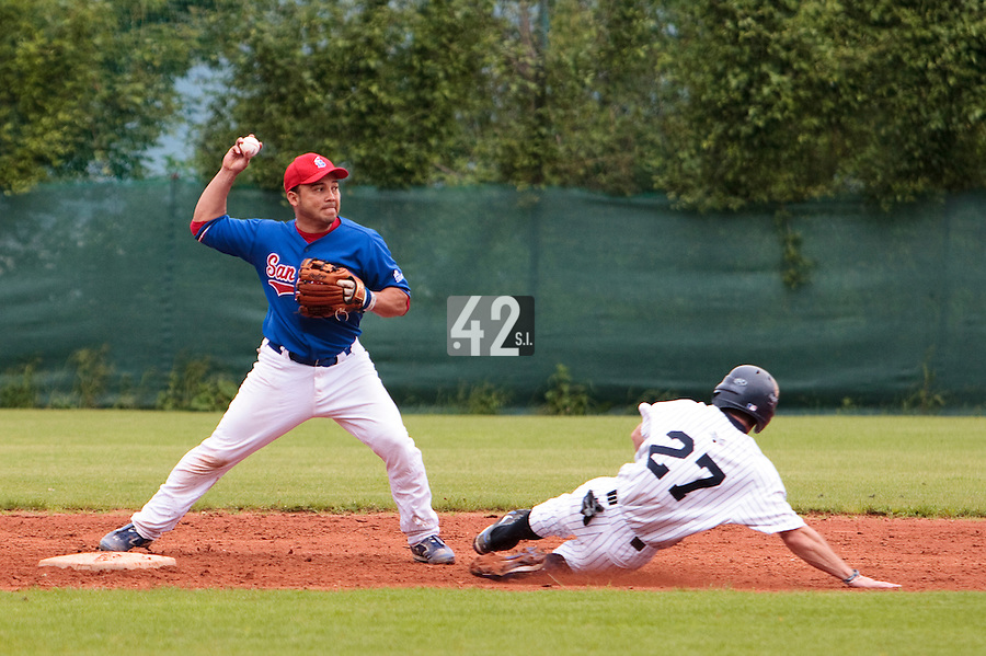 03 June 2010: Juan Manuel Salazar of C.B. Sant Boi throws the ball to first base for the double play over Joris Bert during the 2010 Baseball European Cup match won  8-4 by C.B. Sant Boi over the Rouen Huskies, at the Kravi Hora ballpark, in Brno, Czech Republic.