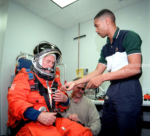 This photo release shows United States Senator John H. Glenn, Jr (Democrat of Ohio) being helped by Lloyd Armintor (center) of Boeing and Carlous Gillis in the donning of his partial-pressure launch and entry suit during training at the Johnson Space Center in Houston, Texas on April 19, 1998. .Credit: NASA via CNP