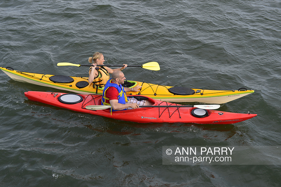 South Merrick, New York, USA. 24th May 2015. A young man and woman are kayaking in Merrick Bay along the south shore of Levy Park & Preserve during the Memorial Day Weekend. The red kayak had Carolina and the yellow kayak had Montauk written on their bows.