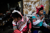 Ethnic minority Hani women sit outside a small restaurant in Xinjie, Yuanyang County, Yunnan Province, China.