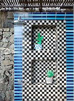 The rough stone walls of an open air shower have been covered in striking ceramic tiles