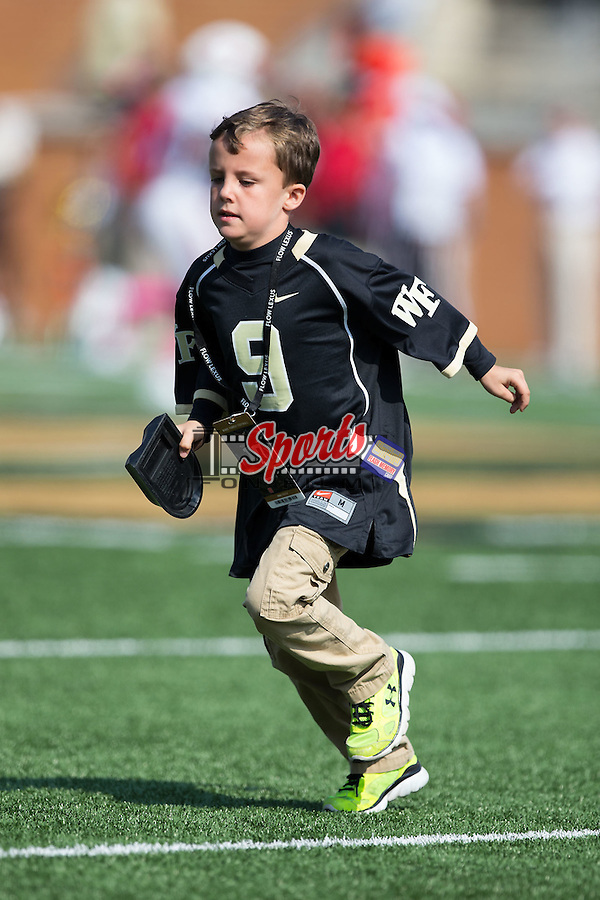 """Deac Haas runs off the field carrying the kick-off tee as the """"Kick-off Kid"""" as the Wake Forest Demon Deacons played host to the North Carolina Tar Heels at BB&T Field on October 24, 2015 in Winston-Salem, North Carolina.  The Wolfpack defeated the Demon Deacons 35-17.   (Brian Westerholt/Sports On Film)"""