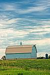 Clouds soar over a white barn in rural America.