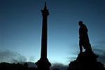 Statue of Henry Havelock and Nelson?s in silhouette, Trafalgar Square, London UK
