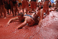 BUNYOL, SPAIN - AUGUST 31: Two men trying to swim immersed in tomato juice in the Tomatina August 31, 2005 in Bunyol, Valencia, Spain. Approximately 45,000 people pelted each other with a little over 100.000 kilograms of tomatoes. The tomatina is known as the world's largest tomato battle. Photo by Ander Gillenea.