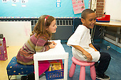 MR / Schenectady, NY. Zoller Elementary School (urban public school). Kindergarten inclusion classroom. Students playing together in house corner at free playtime. Left: girl, 5; right: boy, 6, African American & Puerto Rican American. MR: Cas12, Car38. ID: AM-gKw. © Ellen B. Senisi.