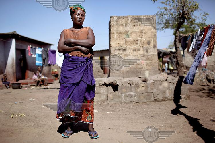Alice Mulopa (48) stands beside her toilet in Kanyama.