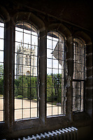 The house stands in an elevated position in the Lincolnshire countryside adjacent to the chuch of the Holy Cross with its decorated battlements and eight pinnacles, seen here from the house through arched mullion windows