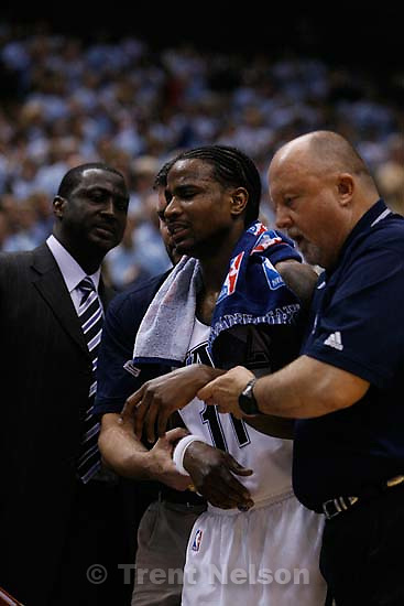 Gary Briggs (right) and Brian Zettler held Utah Jazz guard Dee Brown (11) off the court after he hit the floor hard. Salt Lake City - Utah Jazz vs. Golden State Warriors, NBA Playoffs basketball, second round, Game Two, at EnergySolutions Arena.