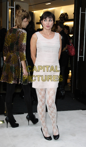 JEMIMA FRENCH (background) & SADIE FROST.Vogue 'Fashion's Night Out ' launch at Burberry's store in New Oxford Street, London, England..September 10th 2009.full length beige sleeveless dress top lace tights pattern black pumps shoes flats  gold velvet purple green back behind rear .CAP/ROS.©Steve Ross/Capital Pictures.